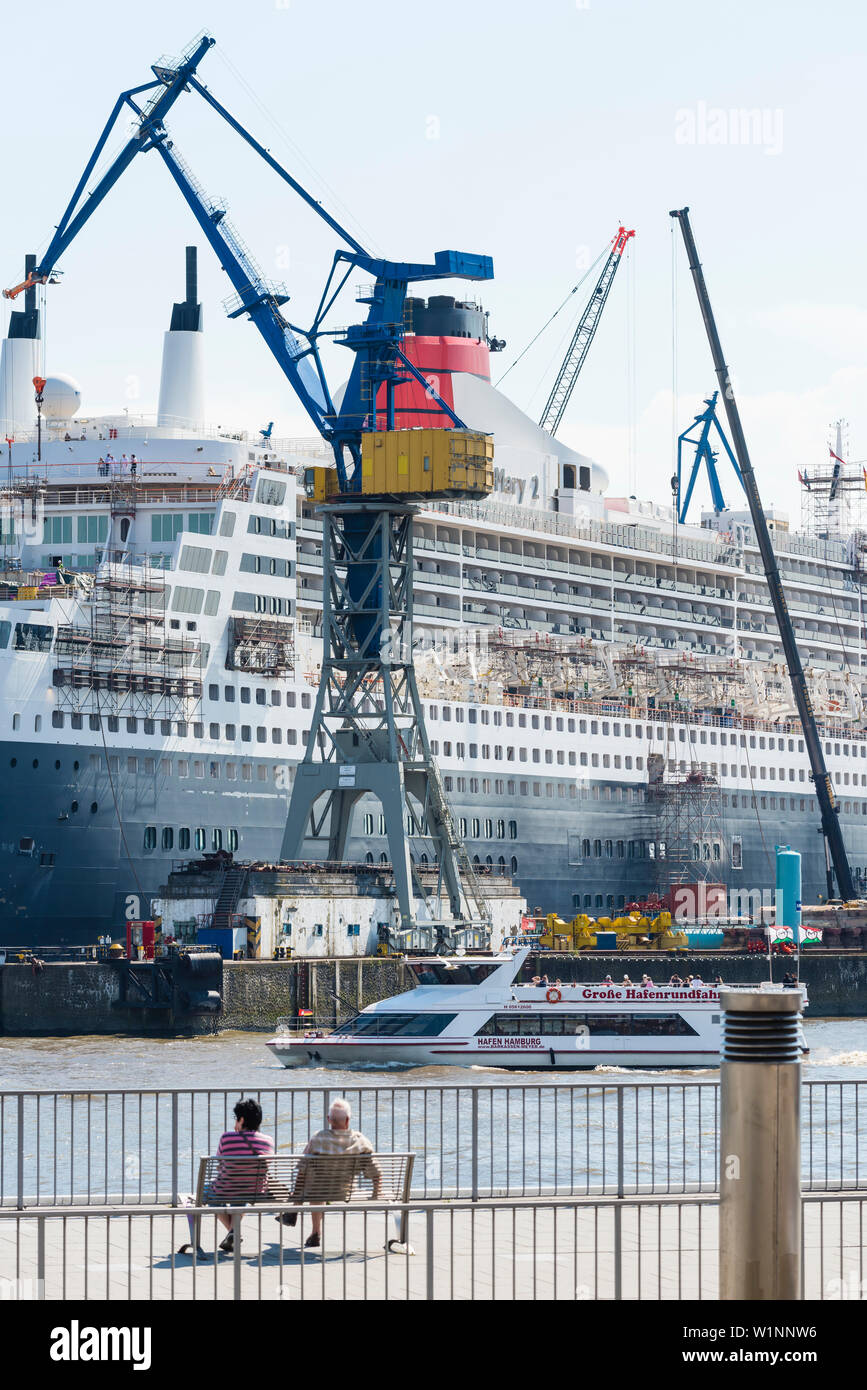 A pair sitting at the landing stages in front of the dry dock of the shipyard Blohm and Voss where the cruise ship QE2 is being overhault, Hamburg, Ge - Stock Image