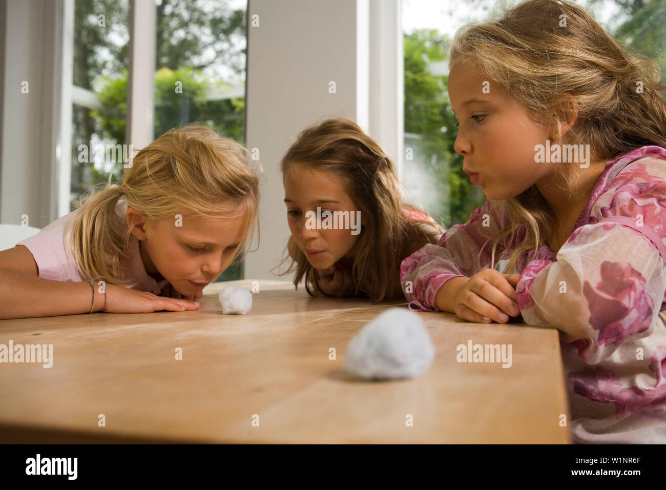 Three girls playing Blowing Cotton Wool, children's birthday party - Stock Image