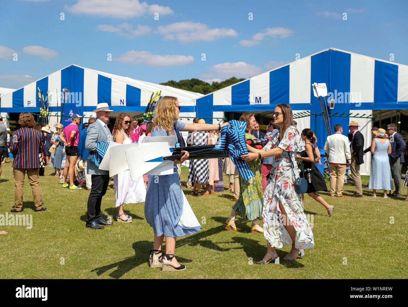 Women carrying oars on the opening day of the 2019 Henley Royal Regatta alongside the river Thames. - Stock Image