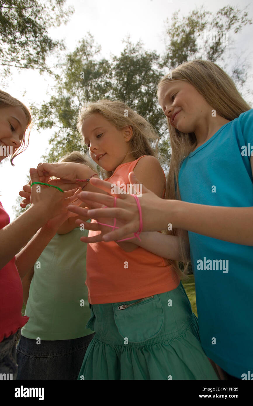 Three girls playing cat's cradle, children's birthday party - Stock Image