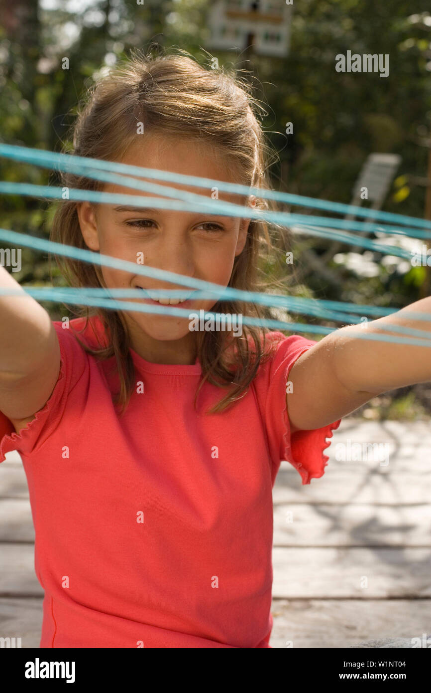 Girl playing cat's cradle, children's birthday party - Stock Image
