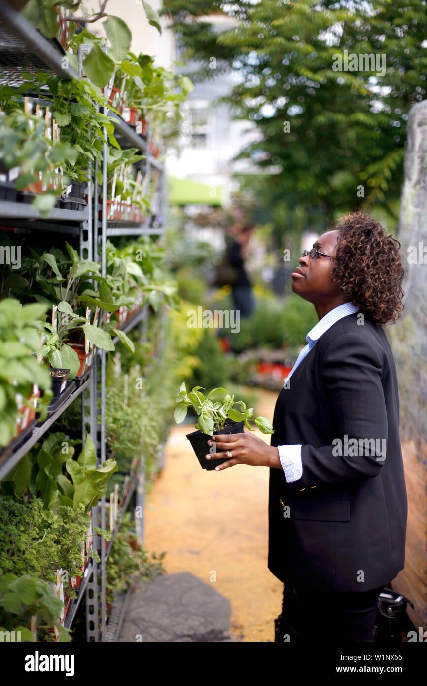 A Woman Buying Plants In A Garden Shop Garden District