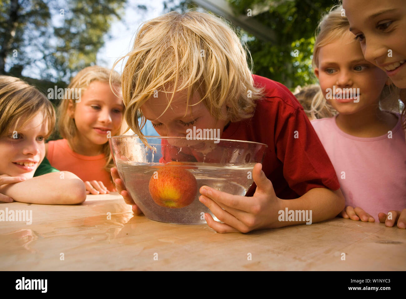 Boy trying to bite off an apple in a dish with water, children's birthday party - Stock Image