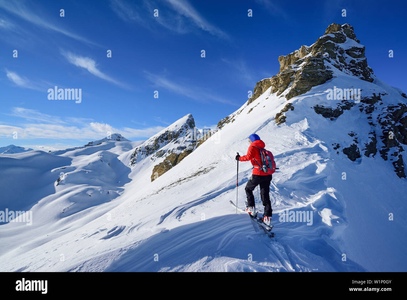 Woman back-country skiing ascending towards Monte Soubeyran, in background Tete Peymian, Punta della Reculaye and Aiguille de Barsin, Monte Soubeyran, - Stock Image