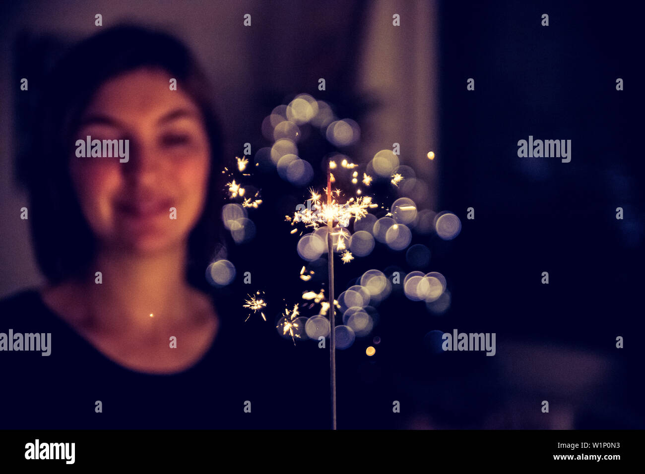 Smiling girl is holding a sparkler in her hand, indoor, lights in background - Stock Image