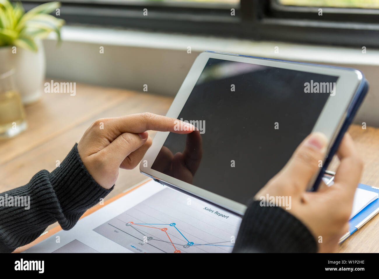 Close up of woman hands holding and tapping tablet screen - Stock Image