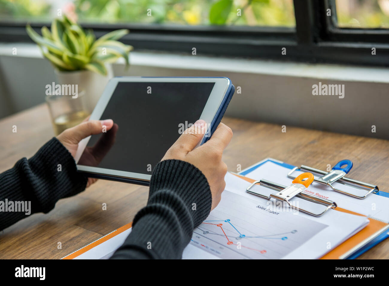 Close up of woman hand using tablet at office desk - Stock Image