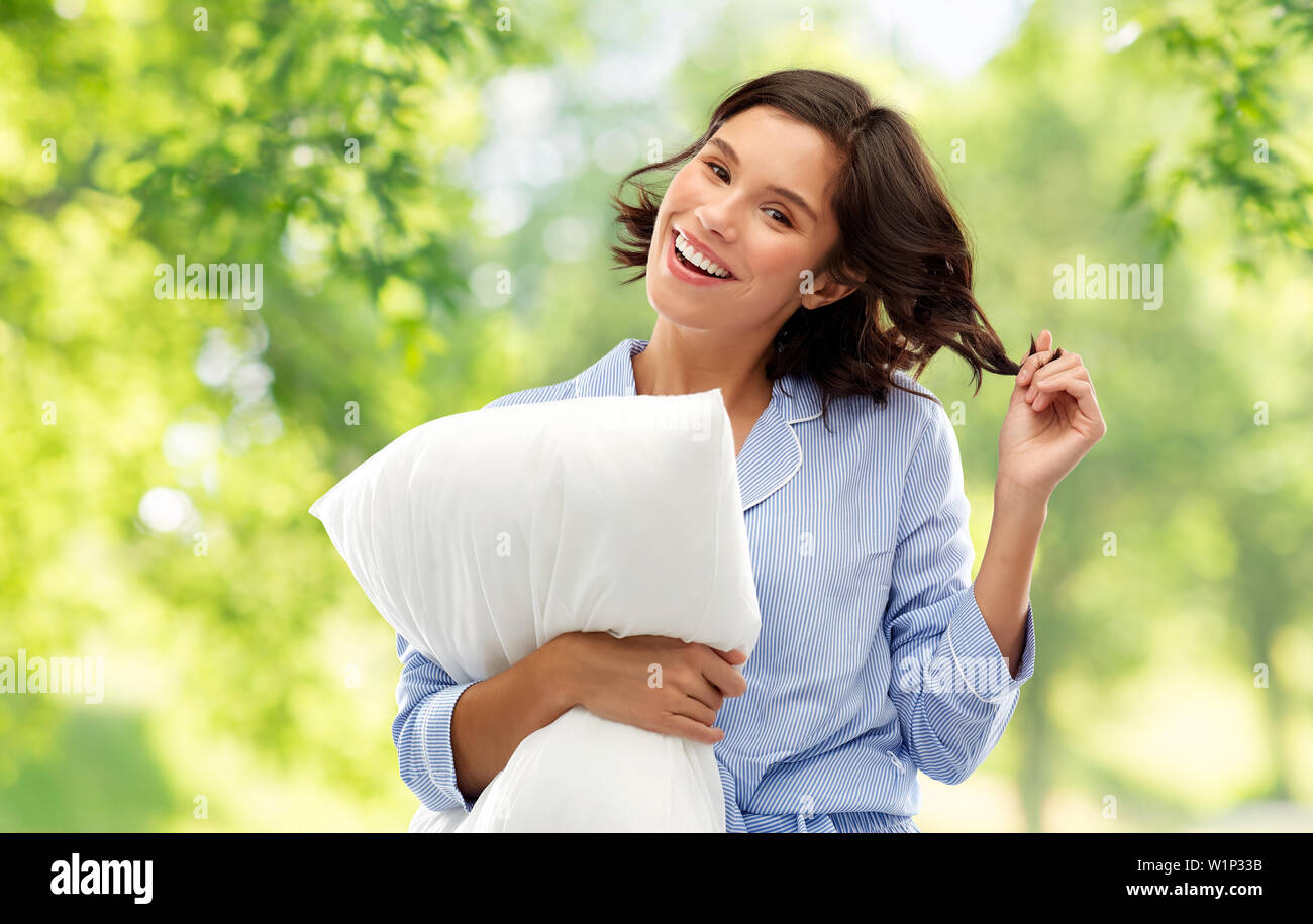 happy young woman in pajama with pillow - Stock Image