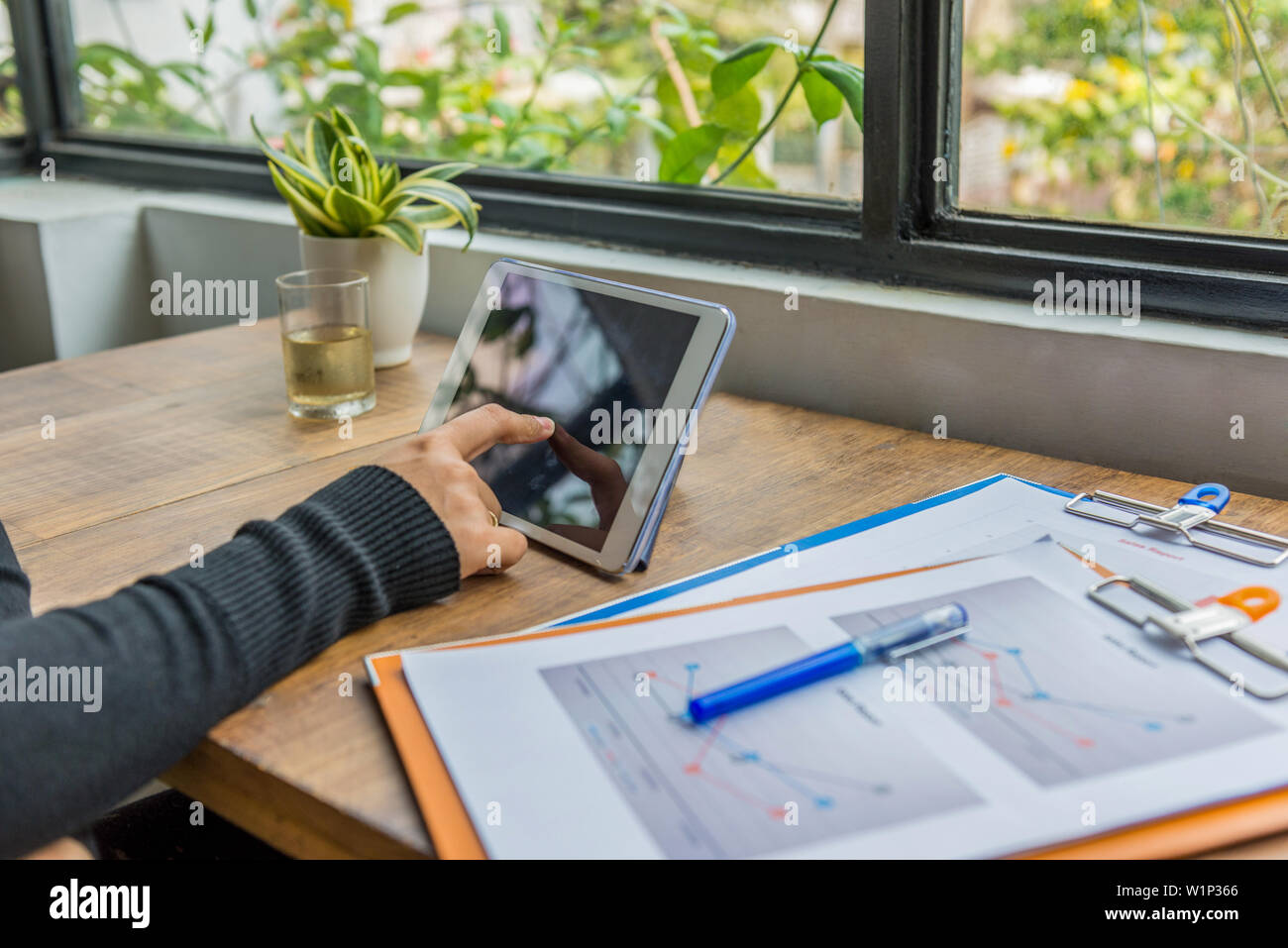Female hand tapping tablet screen at workplace next to window - Stock Image