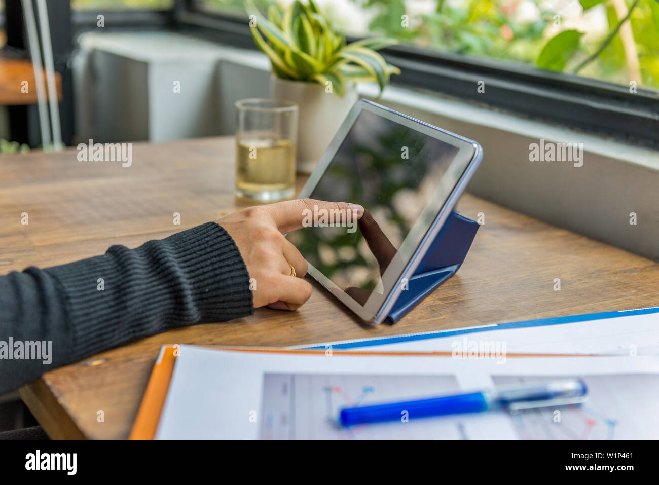 Closeup of index finger tapping tablet screen on wooden table - Stock Image