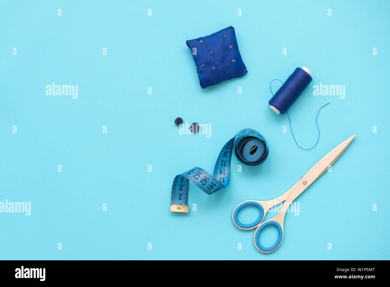 Sewing accessories with threads, scissors, pins, fabric, buttons and sewing tape on blue background. Top view. Flat lay. Stock Photo
