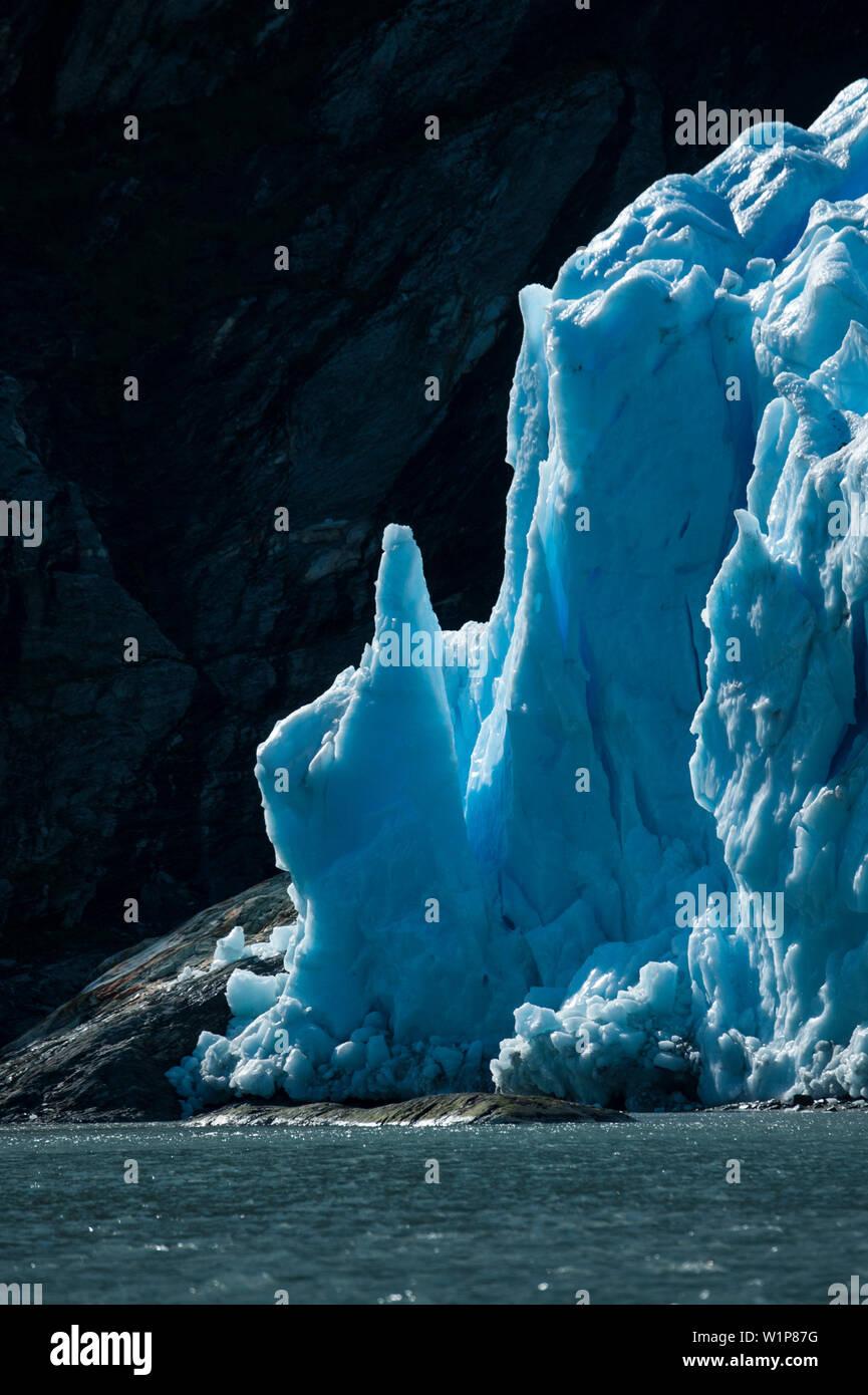 Towers of blue ice shine at the glacier edge, Garibaldi Glacier, near Beagle Canal, Alberto de Agostini National Park, Magallanes y de la Antartica Ch - Stock Image