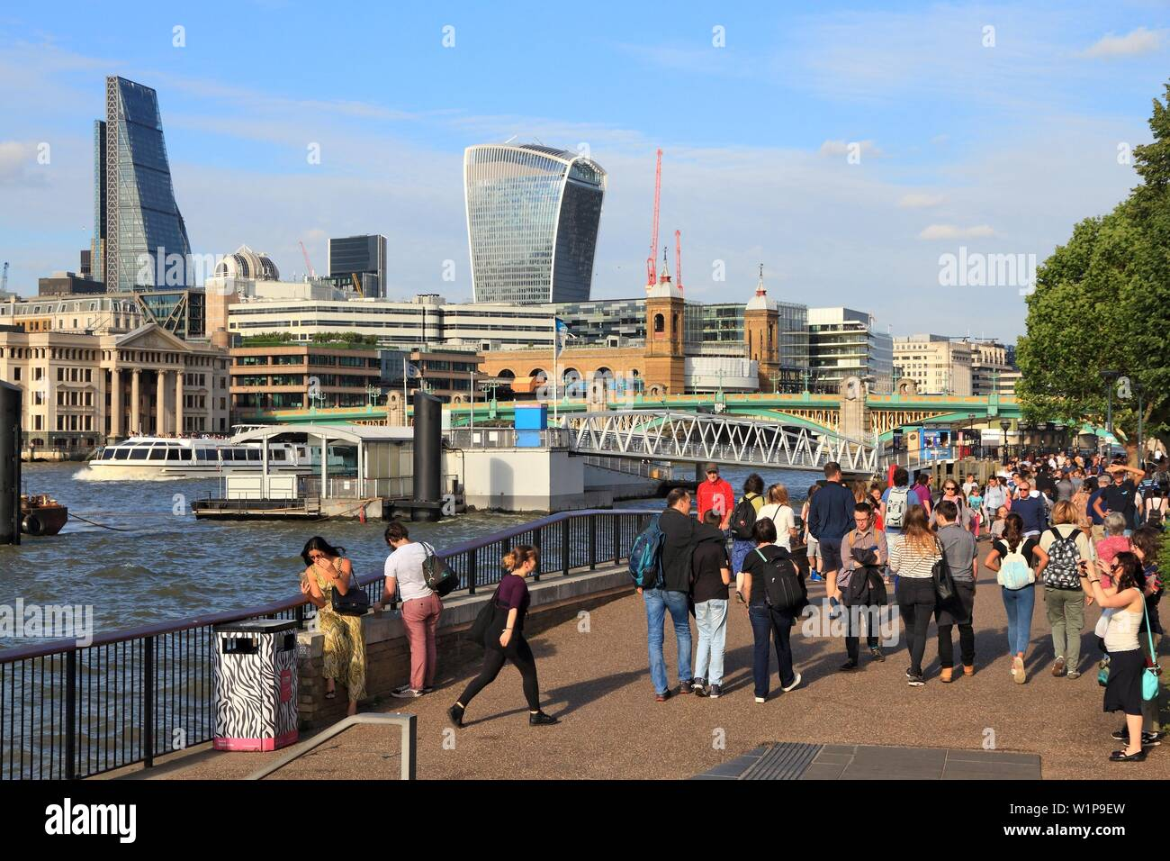 LONDON, UK - JULY 8, 2016: People walk along London Embankment in the UK. London is the most populous city in the UK with 13 million people living in - Stock Image