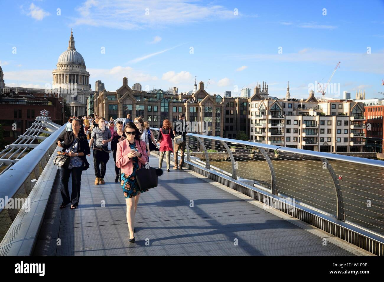LONDON, UK - JULY 8, 2016: People cross the Millennium Bridge in the UK. London is the most populous city in the UK with 13 million people living in i - Stock Image