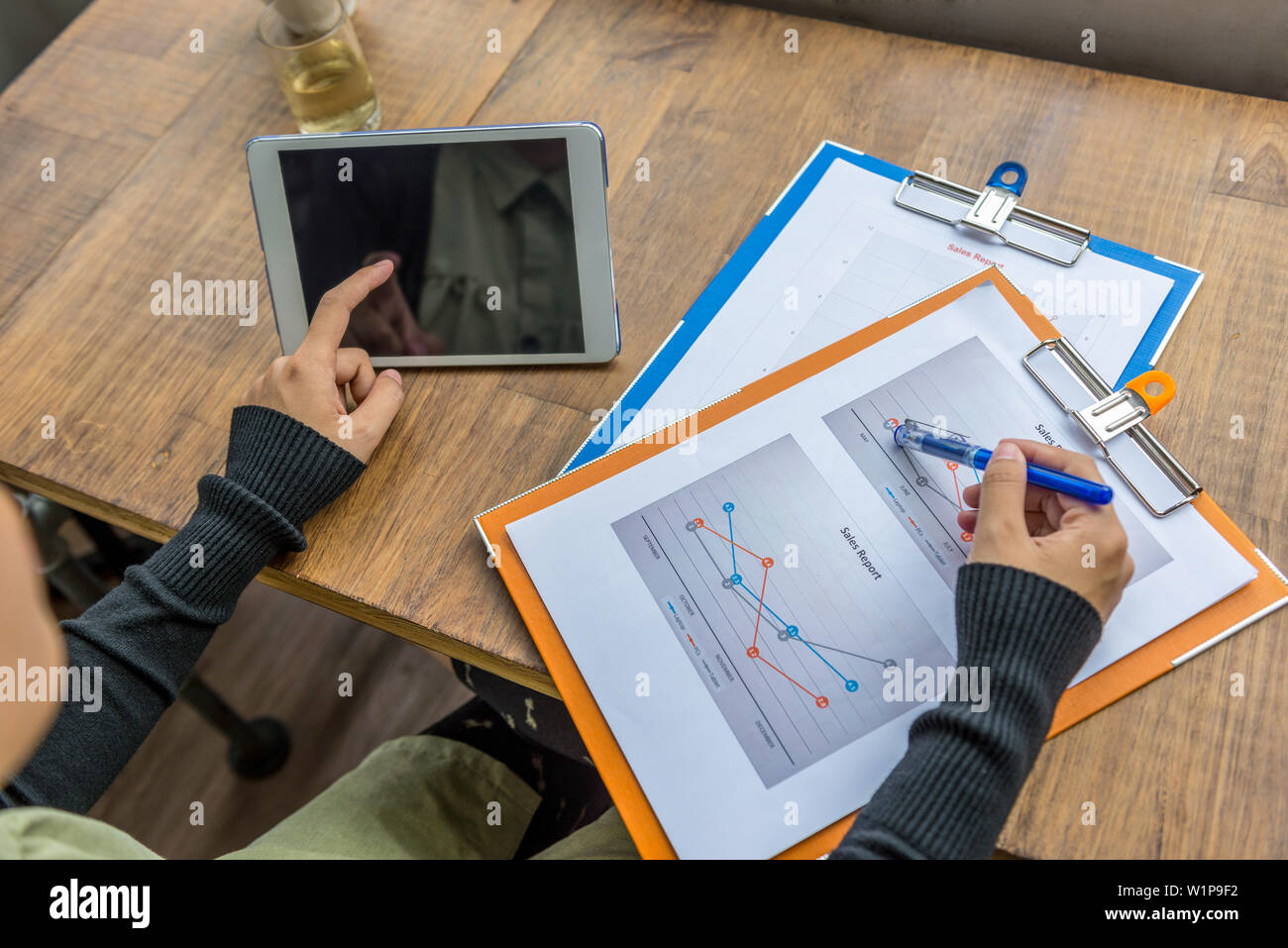 Woman hand pointing tablet screen and statistic diagram document - Stock Image