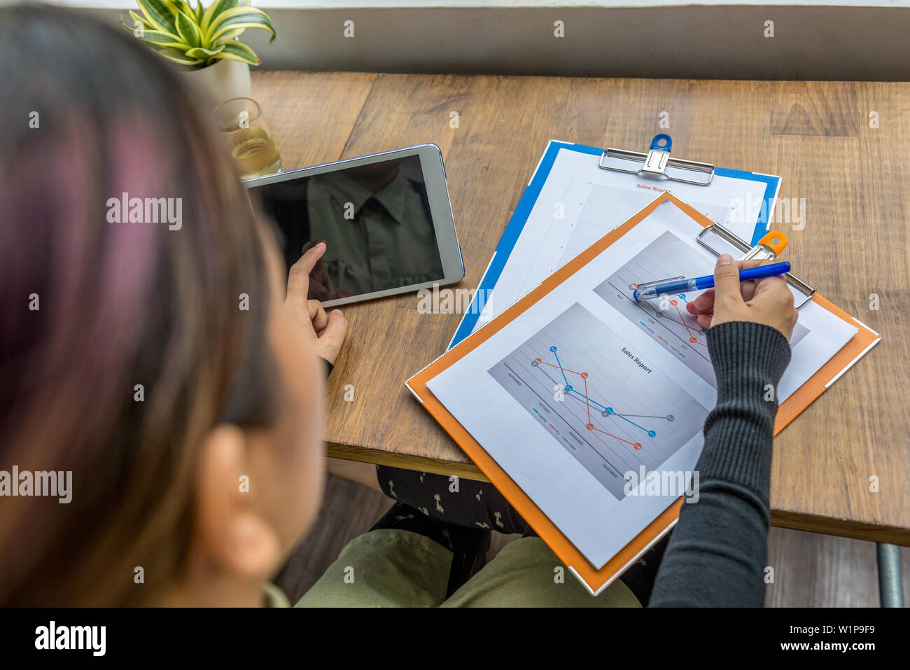 Top view of woman using tablet and pointing at diagram - Stock Image