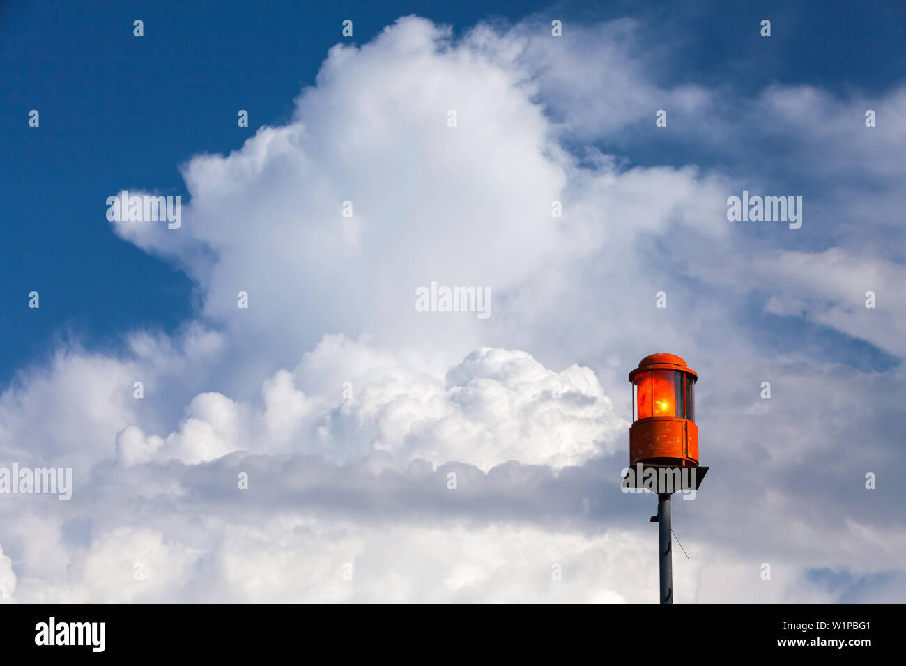 Storm warning light on the Chiemsee in Prien, behind white clouds in the blue sky Stock Photo