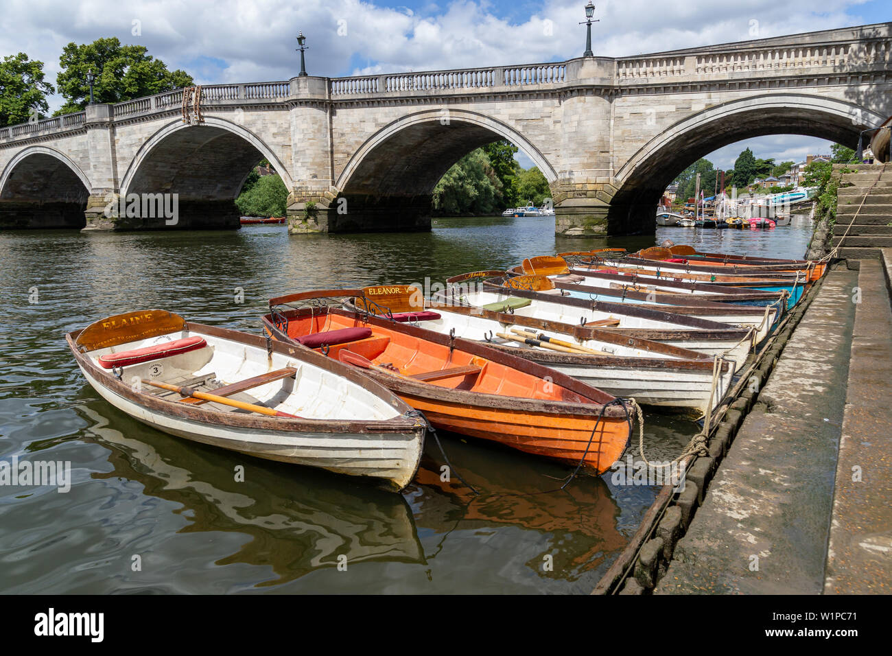 LONDON, UK - JULY 02, 2019. Wooden boats of Richmond Bridge Boat Hire company moored on the River Thames, Richmond, Surrey, England - Stock Image