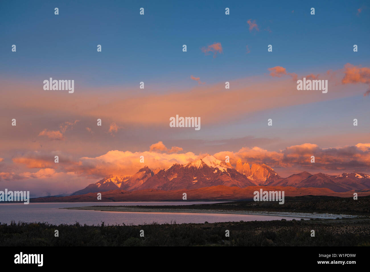 The last light of the sun falls on high craggy snow-covered peaks, Torres del Paine National Park, Magallanes y de la Antartica Chilena, Patagonia, Ch - Stock Image