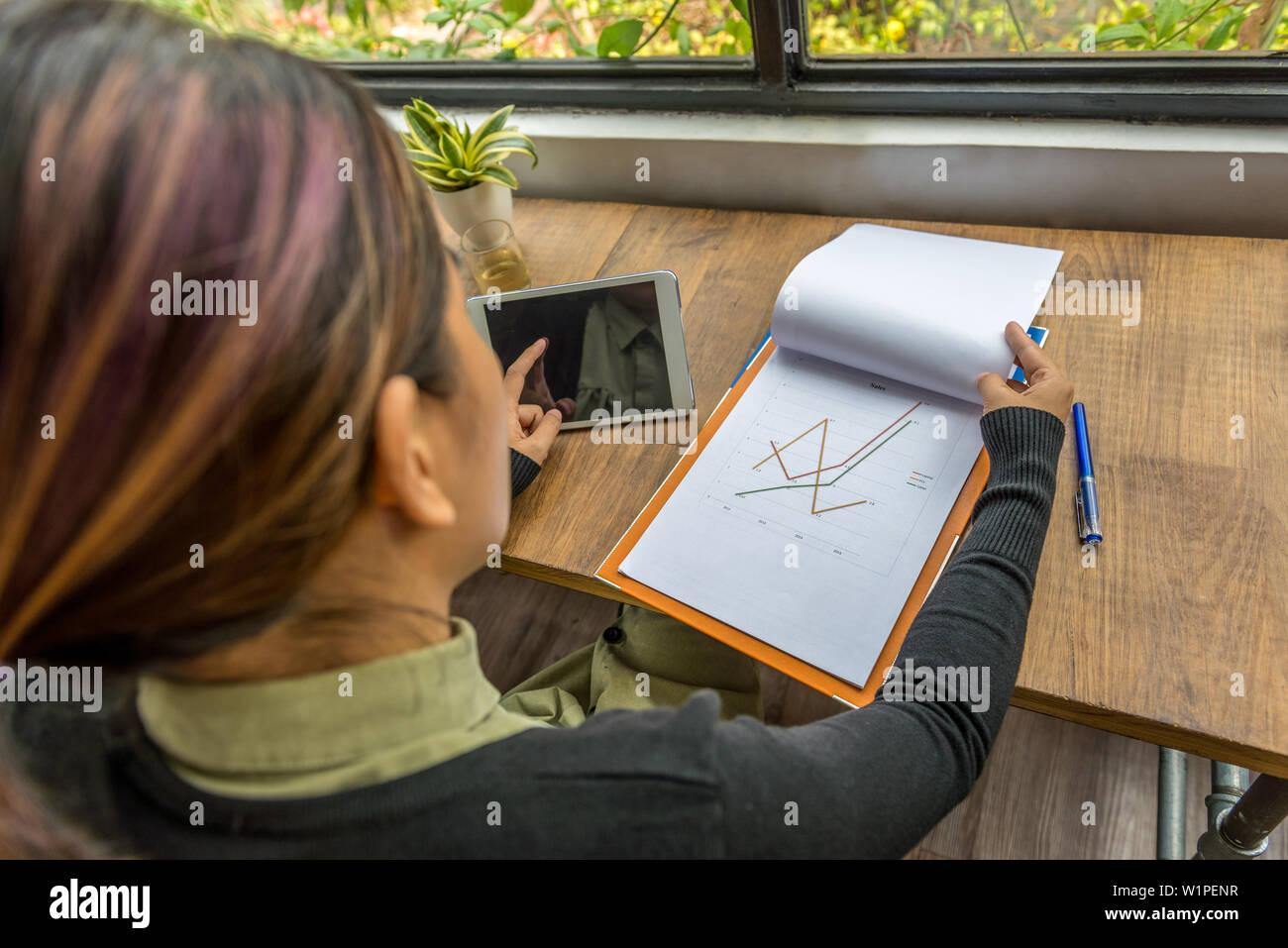 High angle view of freelancer working with tablet and document - Stock Image