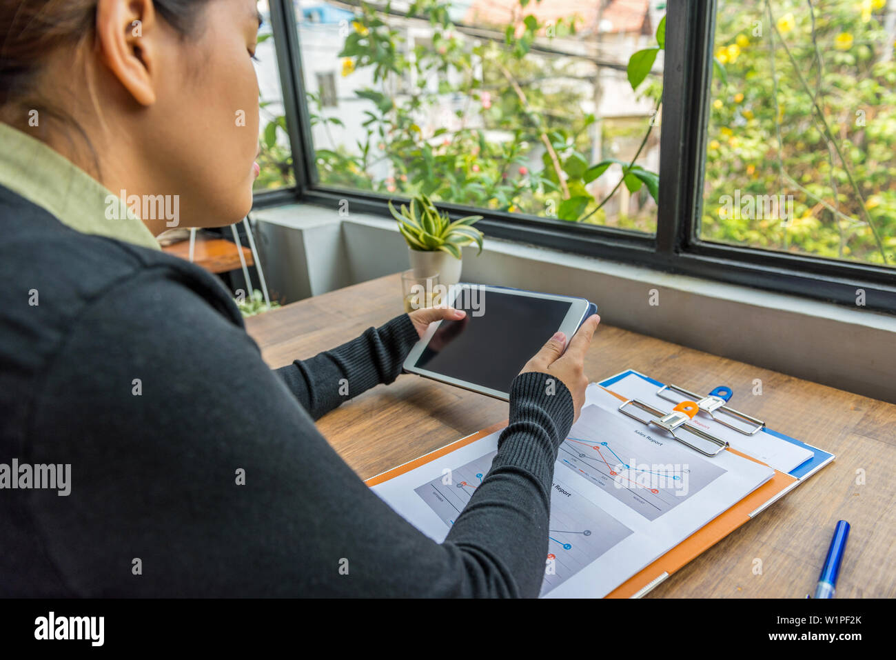 Woman using digital tablet at workplace next to window - Stock Image