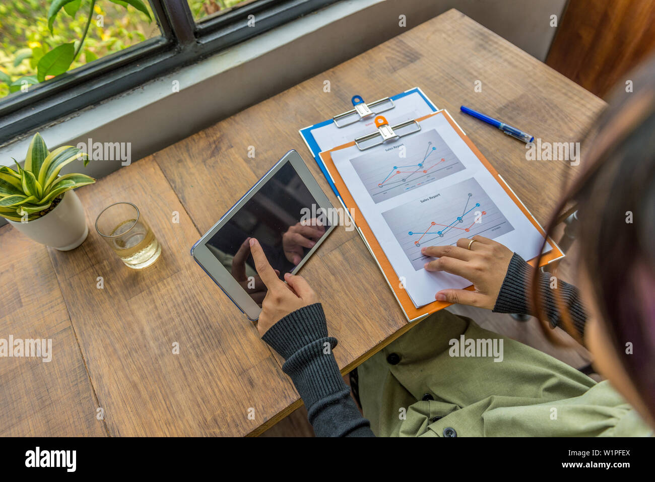 High angle view of woman using tablet, analyzing diagram document - Stock Image