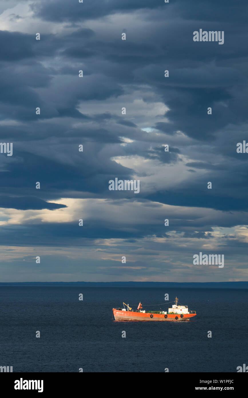The ship Brecknock makes way under a dominating sky of dark, unusual clouds, Punta Arenas, Magallanes y de la Antartica Chilena, Patagonia, Chile, Sou - Stock Image