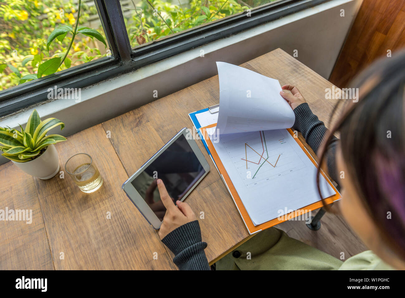 Woman freelancer working on graph document with tablet  - Stock Image