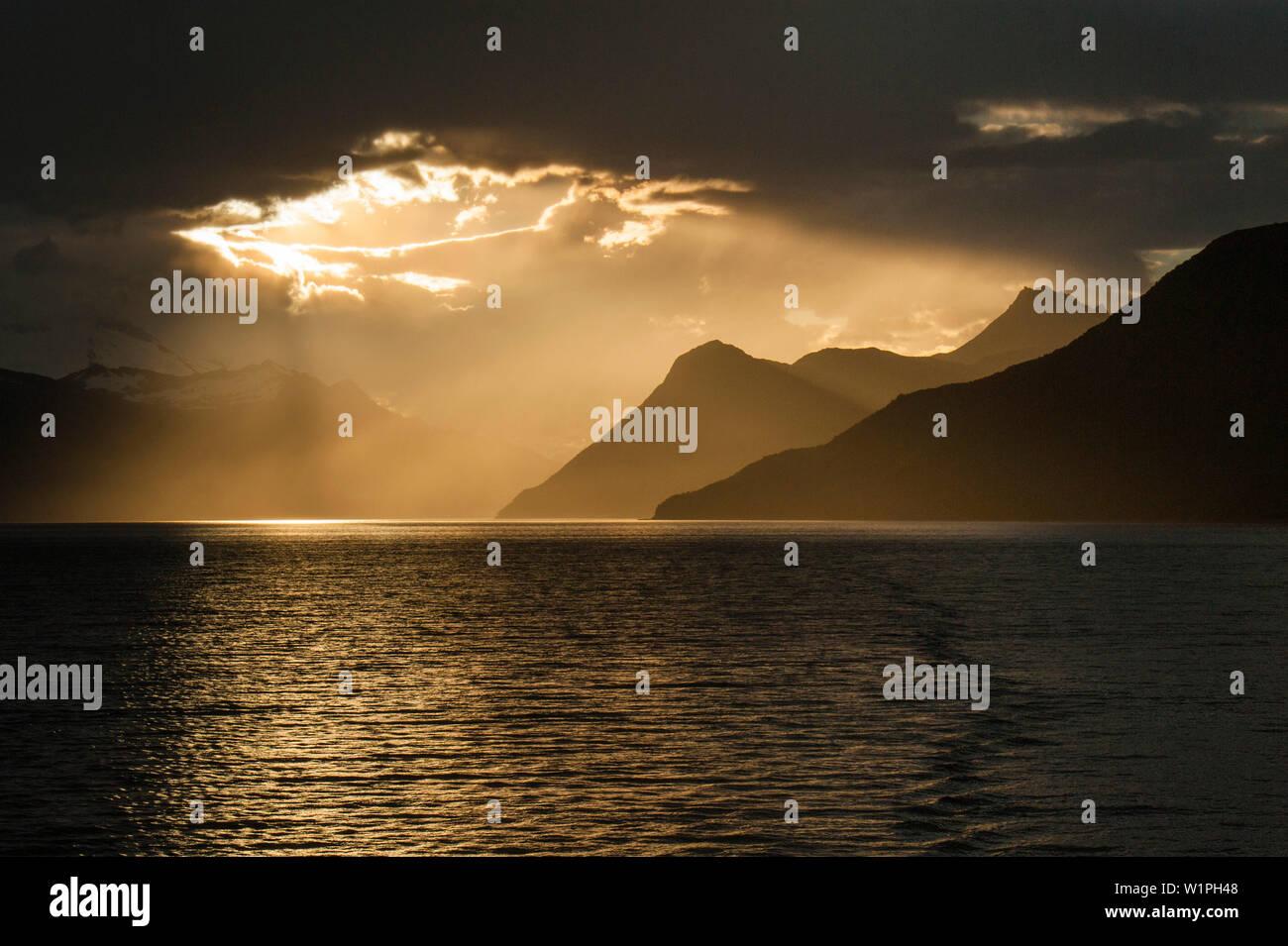 Sun breaks through cloud-cover off the Chilean coast, Beagle Canal, Alberto de Agostini National Park, Magallanes y de la Antartica Chilena, Patagonia - Stock Image