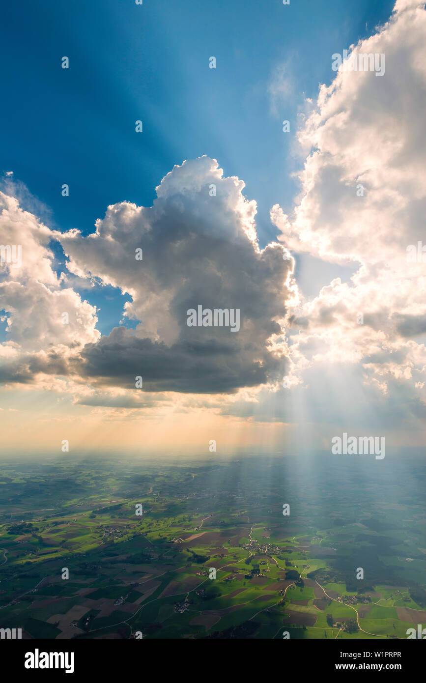 a towering cloud covers up the sun and so creates a dramatic cue state, Bavaria, Germany - Stock Image