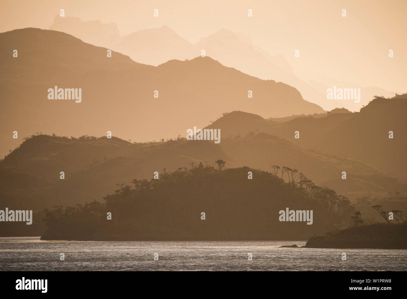 Late-afternoon sun casts a red-orange glow over hills and mountains stacked up in the distance, Strait of Magellan, Magallanes y de la Antartica Chile - Stock Image