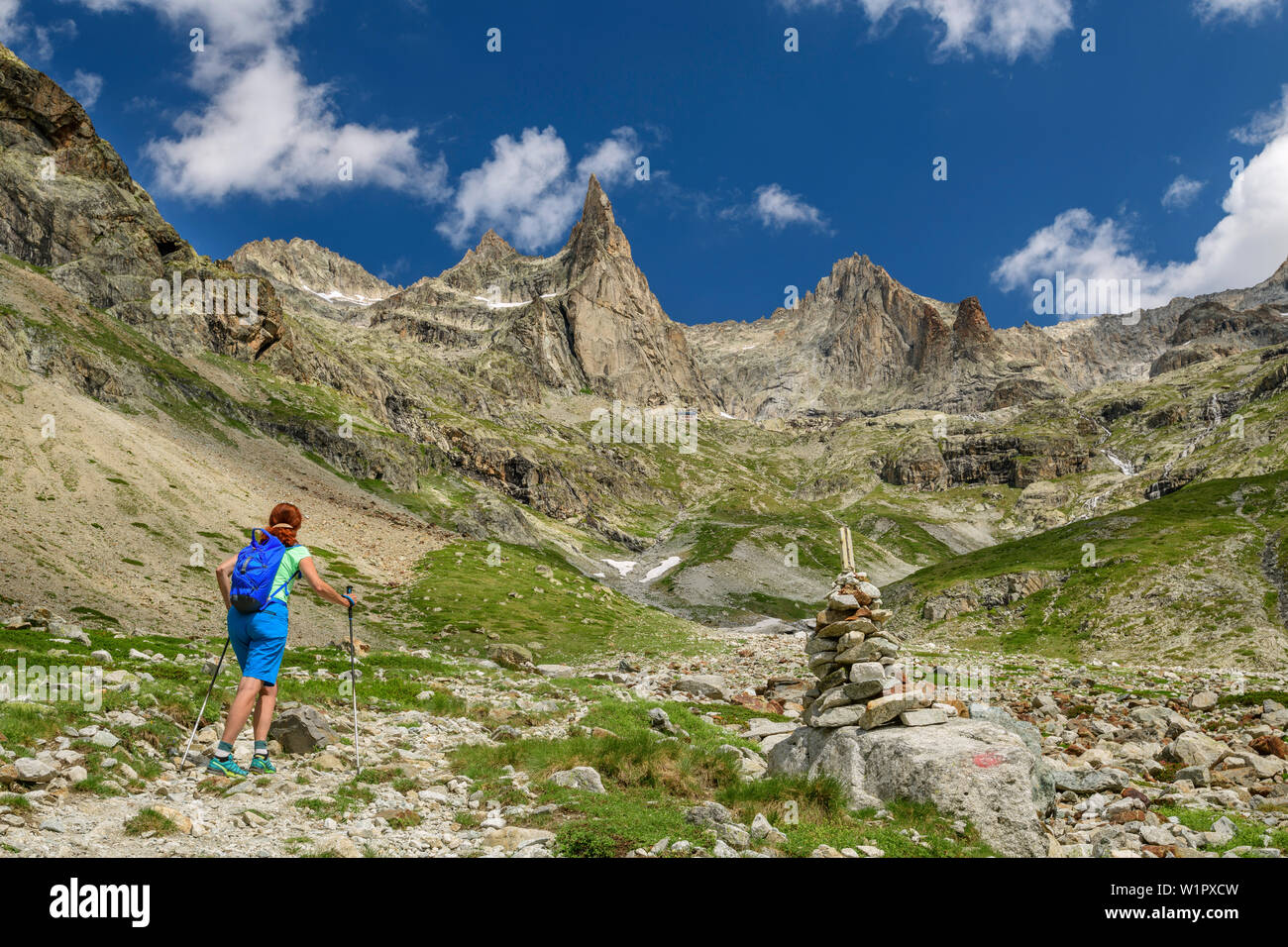 Woman while hiking rises for the refuge du sore Iller, Aiguille Dibona Orientale and Aiguille du sore Iller in the background, Ecrins, Ecrins National - Stock Image