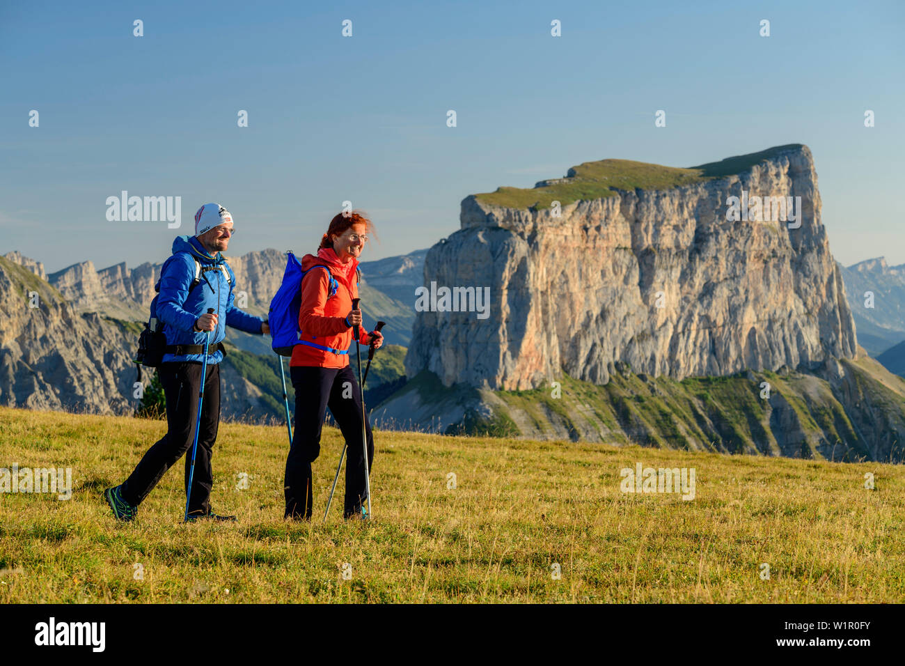A man and a woman walking on meadow with Mont Aiguille in the background, from the Tête Chevalier, Vercors, Dauphine, Dauphine, Isère, France - Stock Image
