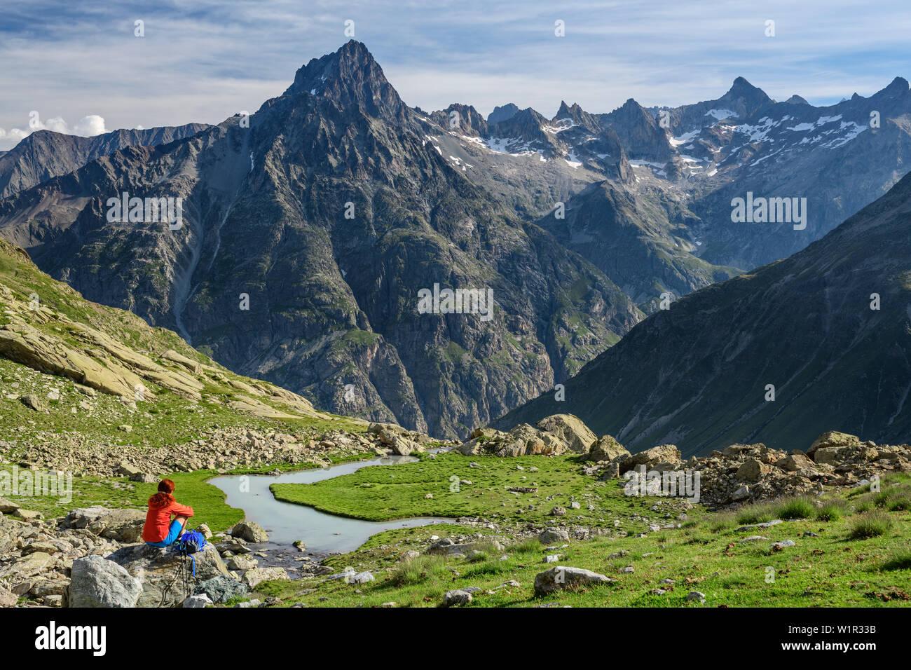 Woman Sitting On rock while hiking and views of Aiguille Du Plat de La Selle, on the Lac Bèches, Ecrins, Ecrins National Park, Dauphiné, Dauphiné, Hau - Stock Image