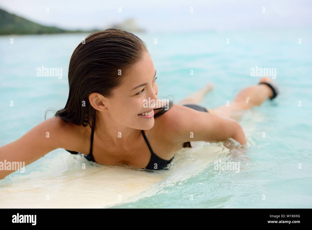 Surfing surfer girl paddle for surf on surfboard. Female bikini woman living healthy active water sports lifestyle on Hawaiian beach. Asian Caucasian model on Waikiki Beach, Oahu, Hawaii. - Stock Image