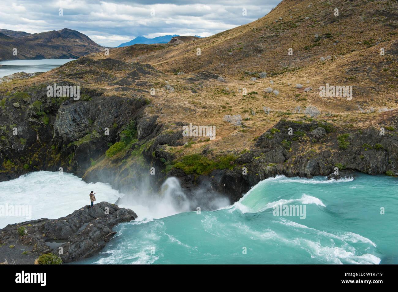 A visitor captures a photo at the Mirador Salto Grande waterfall, Torres del Paine National Park, Magallanes y de la Antartica Chilena, Patagonia, Chi - Stock Image