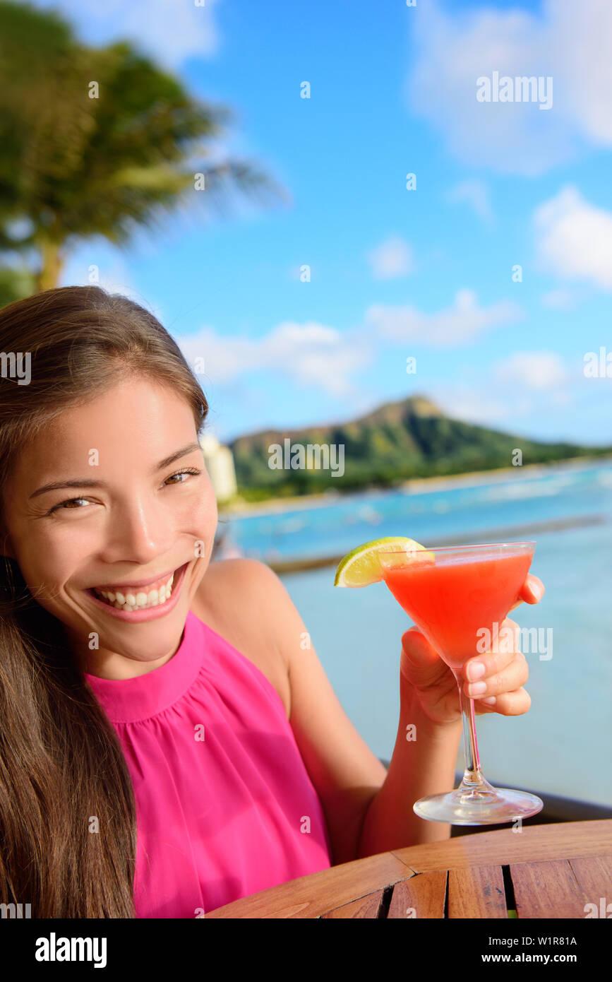 Cocktail woman drinking alcohol drinks at beach bar resort in Waikiki, Honolulu city, Oahu, Hawaii, USA. Asian girl tourist looking at camera toasting a glass of strawberry Hawaiian drink at sunset. Stock Photo
