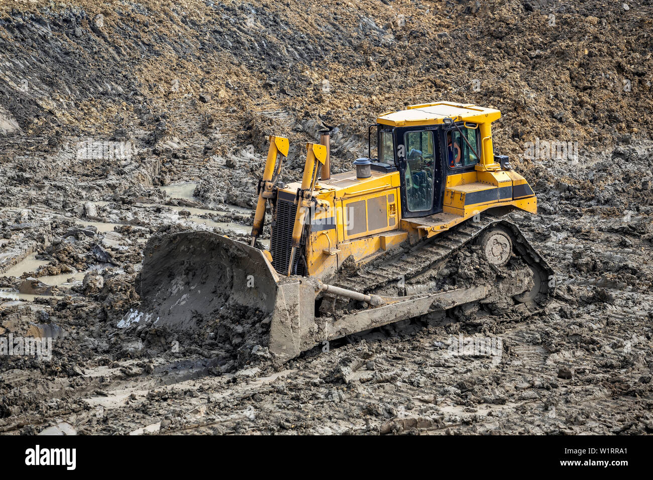 Yellow dozer pushes large piles of dirt on a construction site. - Stock Image
