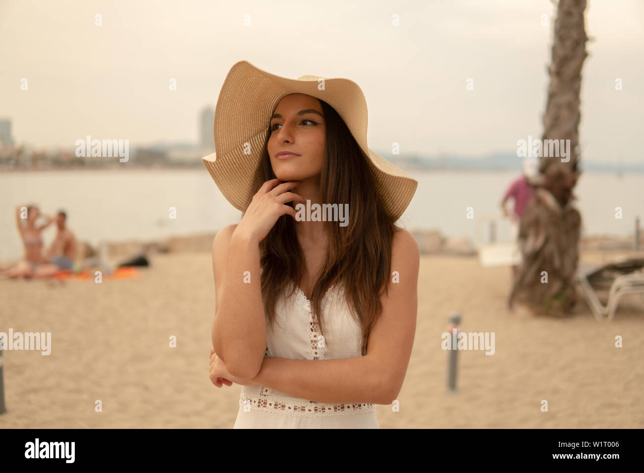 Pretty woman wearing white dress and pamela hat standing Stock Photo