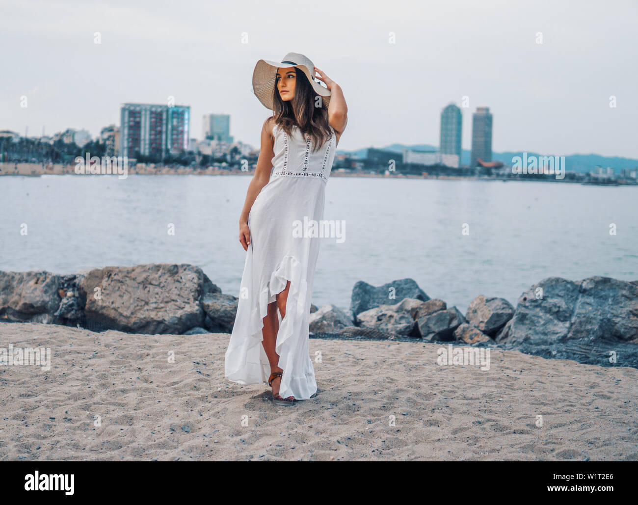Pretty woman wearing white dress and pamela hat standing Stock Photo