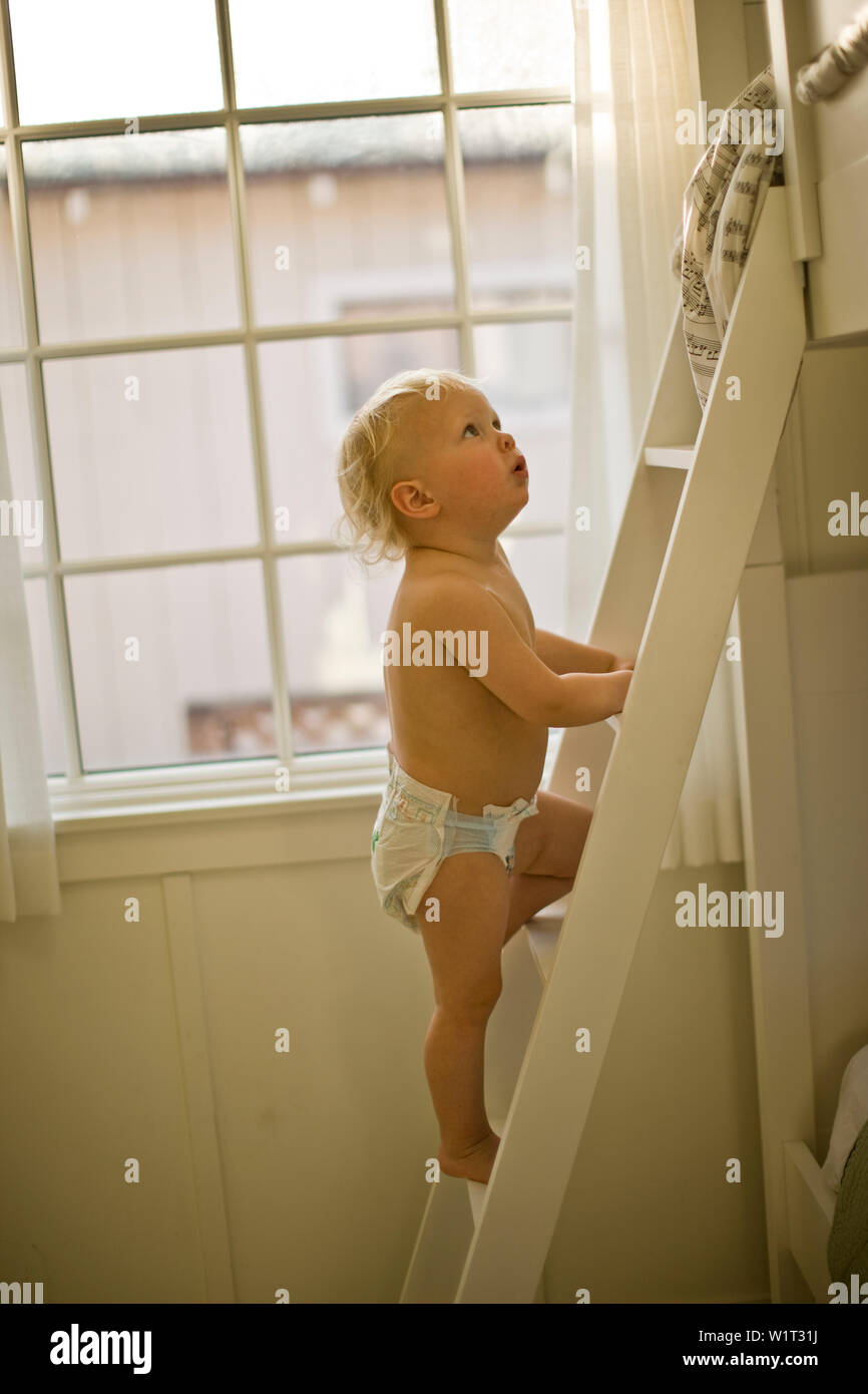 Young toddler climbing the ladder of a bunk bed inside a bedroom. Stock Photo