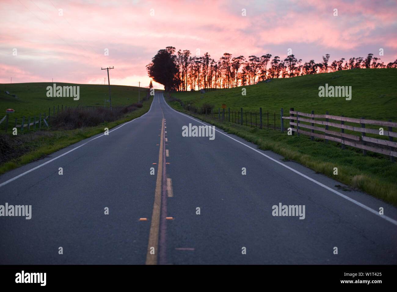 Road stretching into distance at sunset Stock Photo