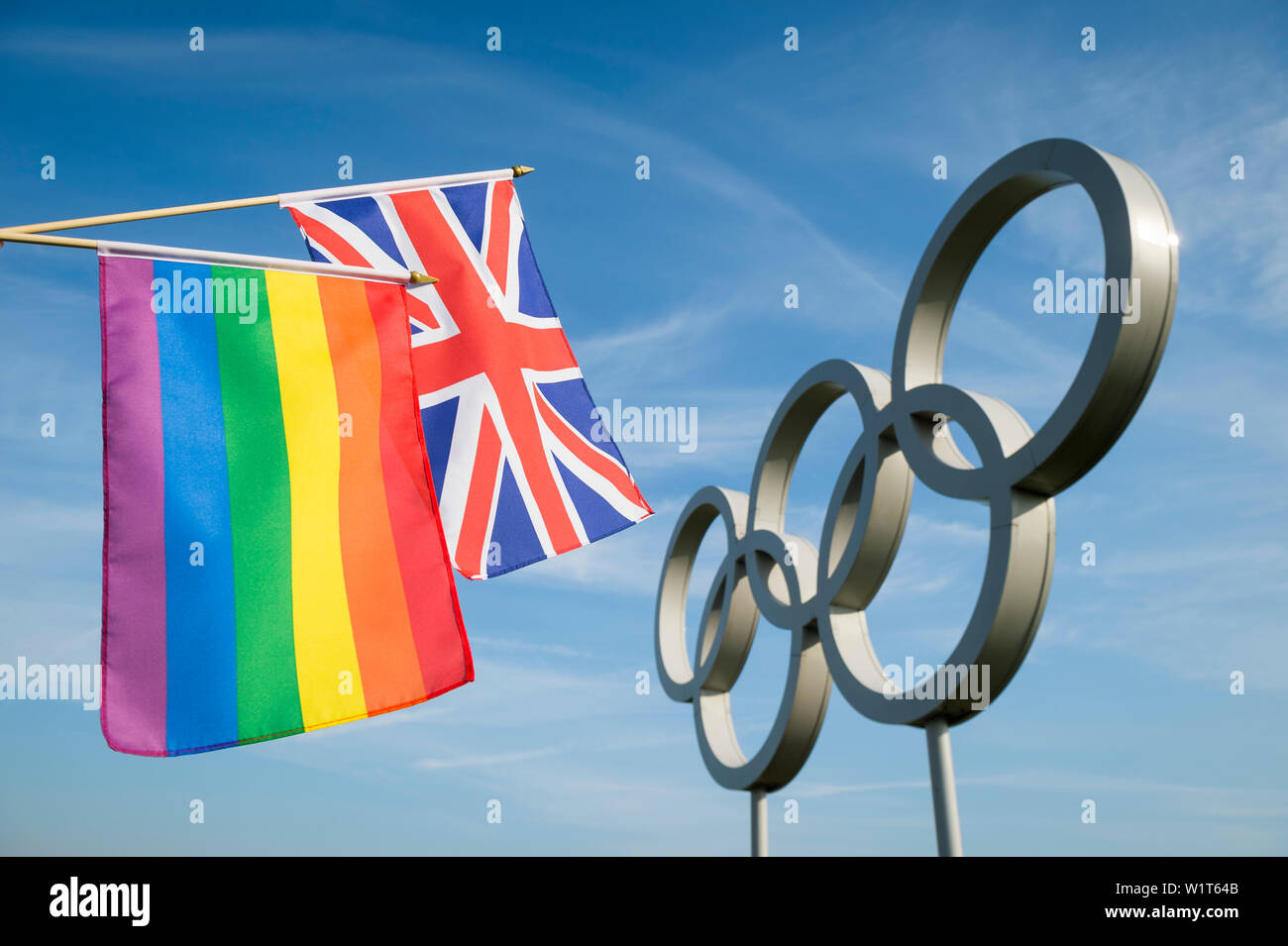 LONDON - MAY 4, 2019: A rainbow colored gay pride flag hangs together with a Japanese flag in front of Olympic Rings against bright blue sky. Stock Photo