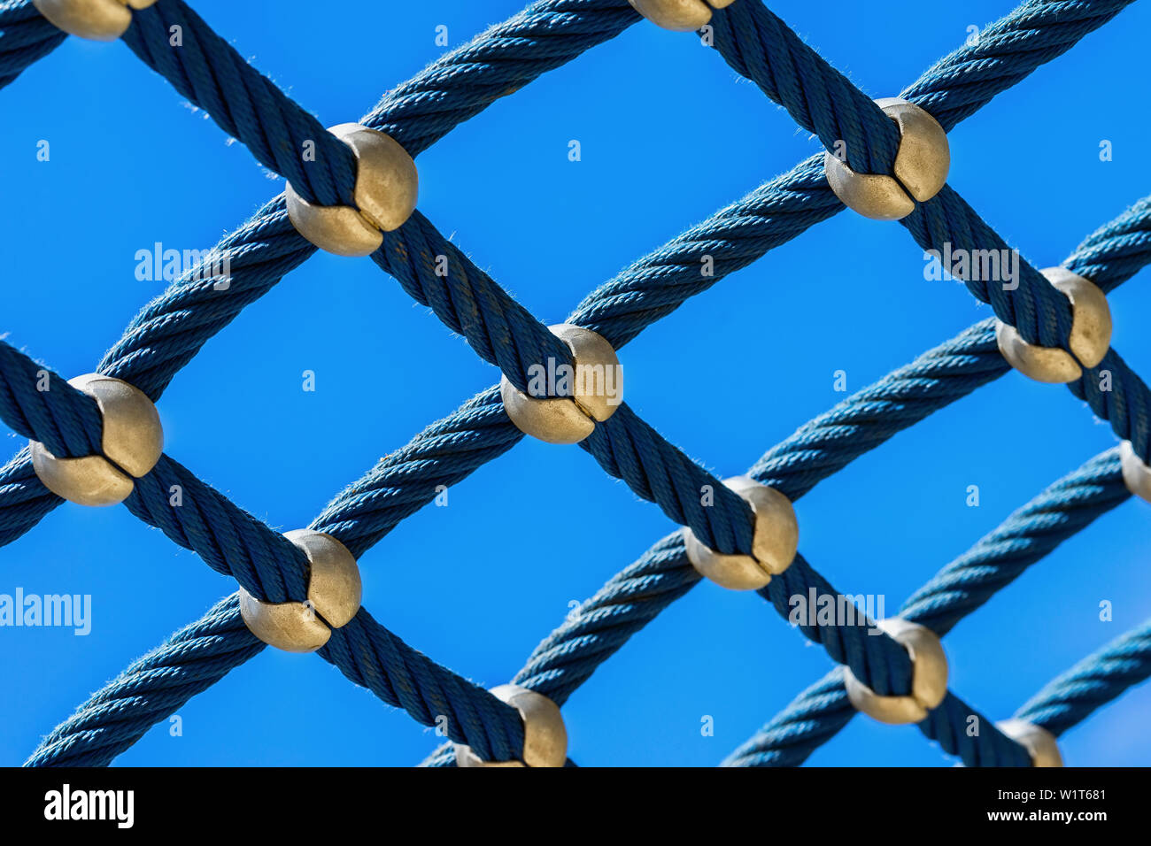 Rope mesh against a bright blue sky closeup, climbing park, playground for play and sport Stock Photo