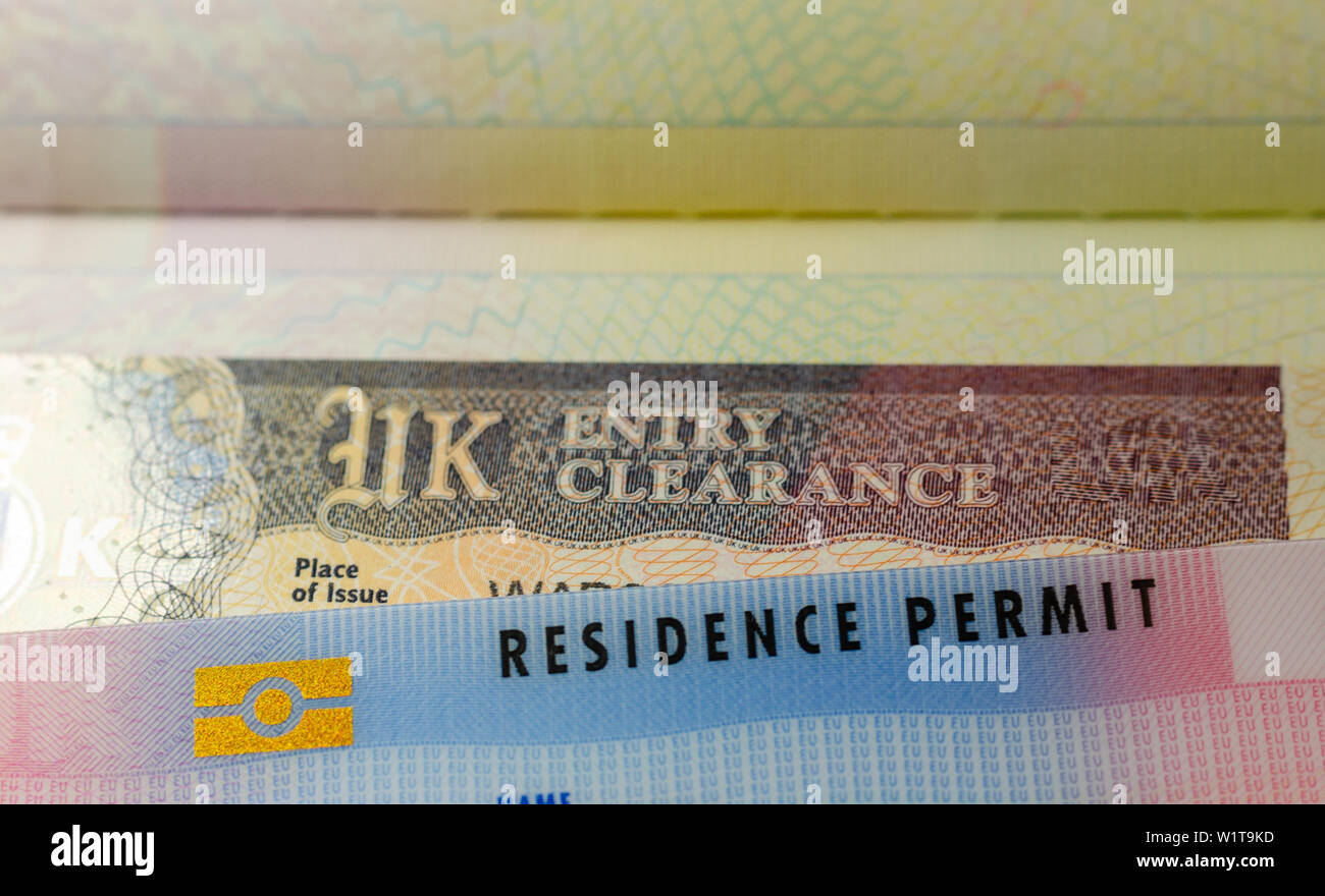 UK BRP (Biometrical Residence Permit) cards for Tier 2 work visa placed on top of UK Entry Clearance vignette sticker in the passport. Stock Photo