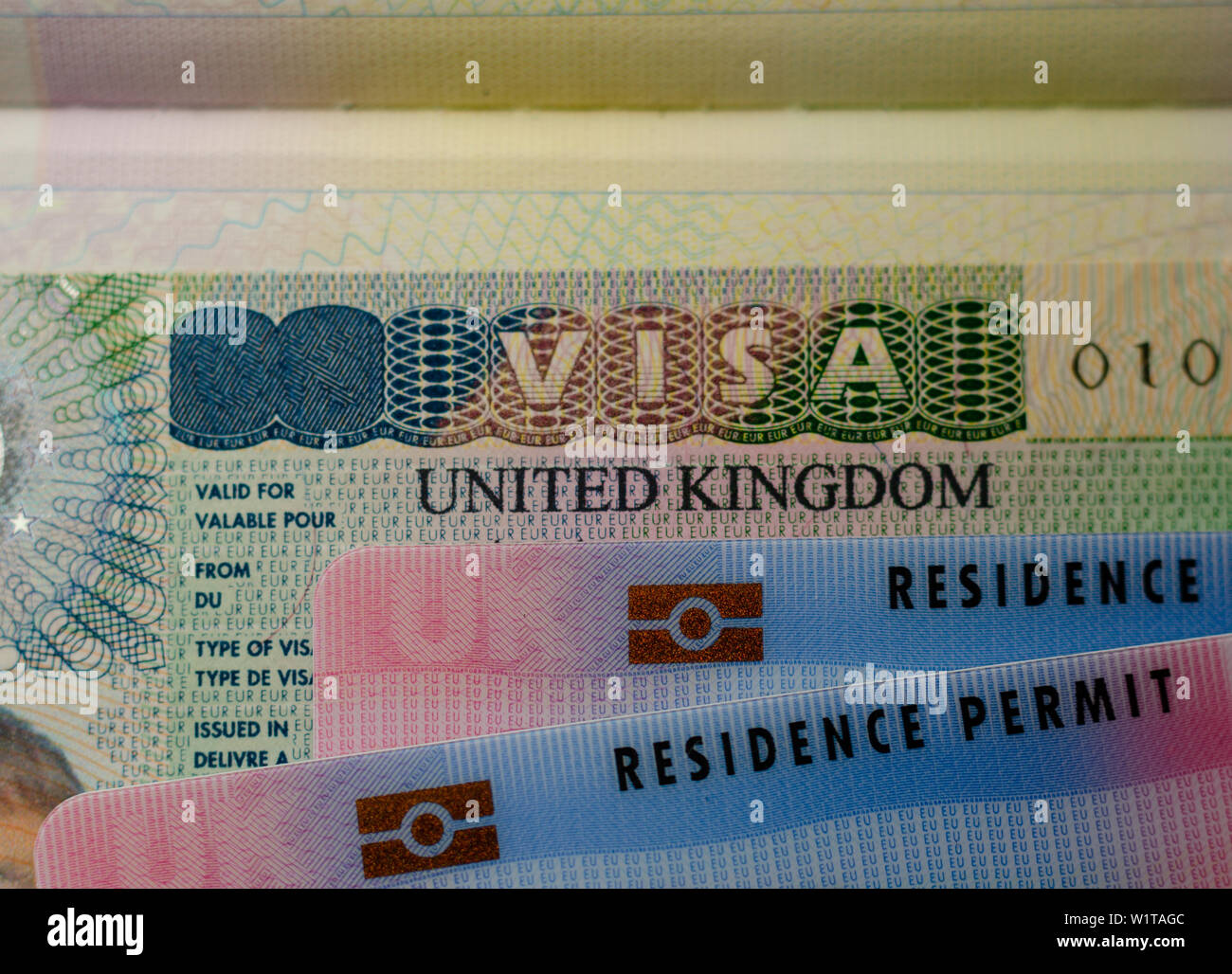 UK BRP cards for Tier 2 work visa placed on top of UK Business VISA sticker in the passport. Close up photo. Stock Photo
