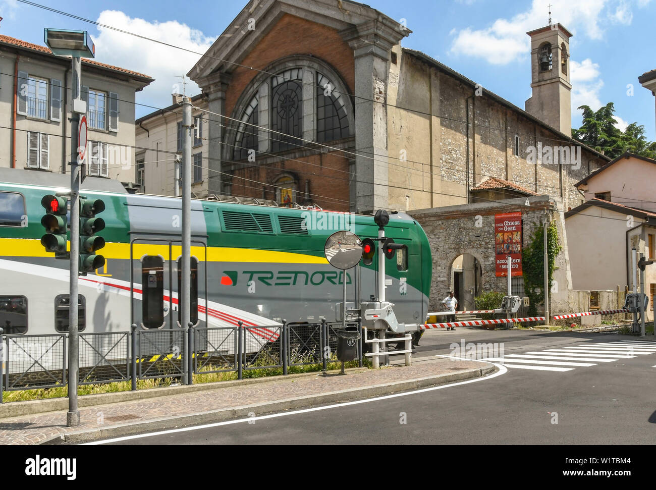 COMO, ITALY - JUNE 2019: Modern electric train passing over a road crossing as it departs from the town of Como on Lake Como Stock Photo