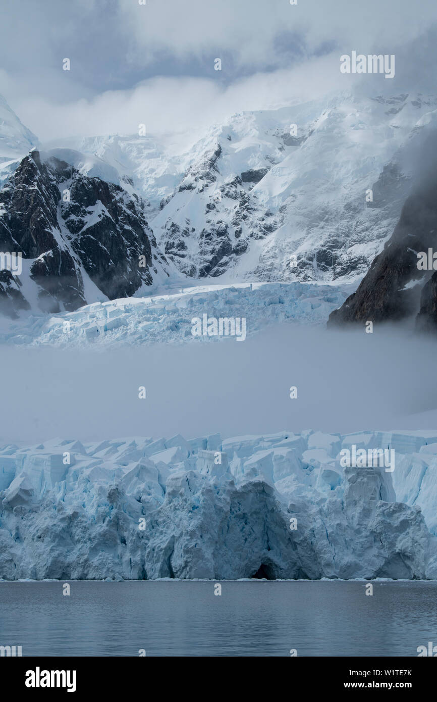 Fog cuts through the middle of a glacier crowned by mountains and clouds, Paradise Bay (Paradise Harbor), Danco Coast, Graham Land, Antarctica Stock Photo