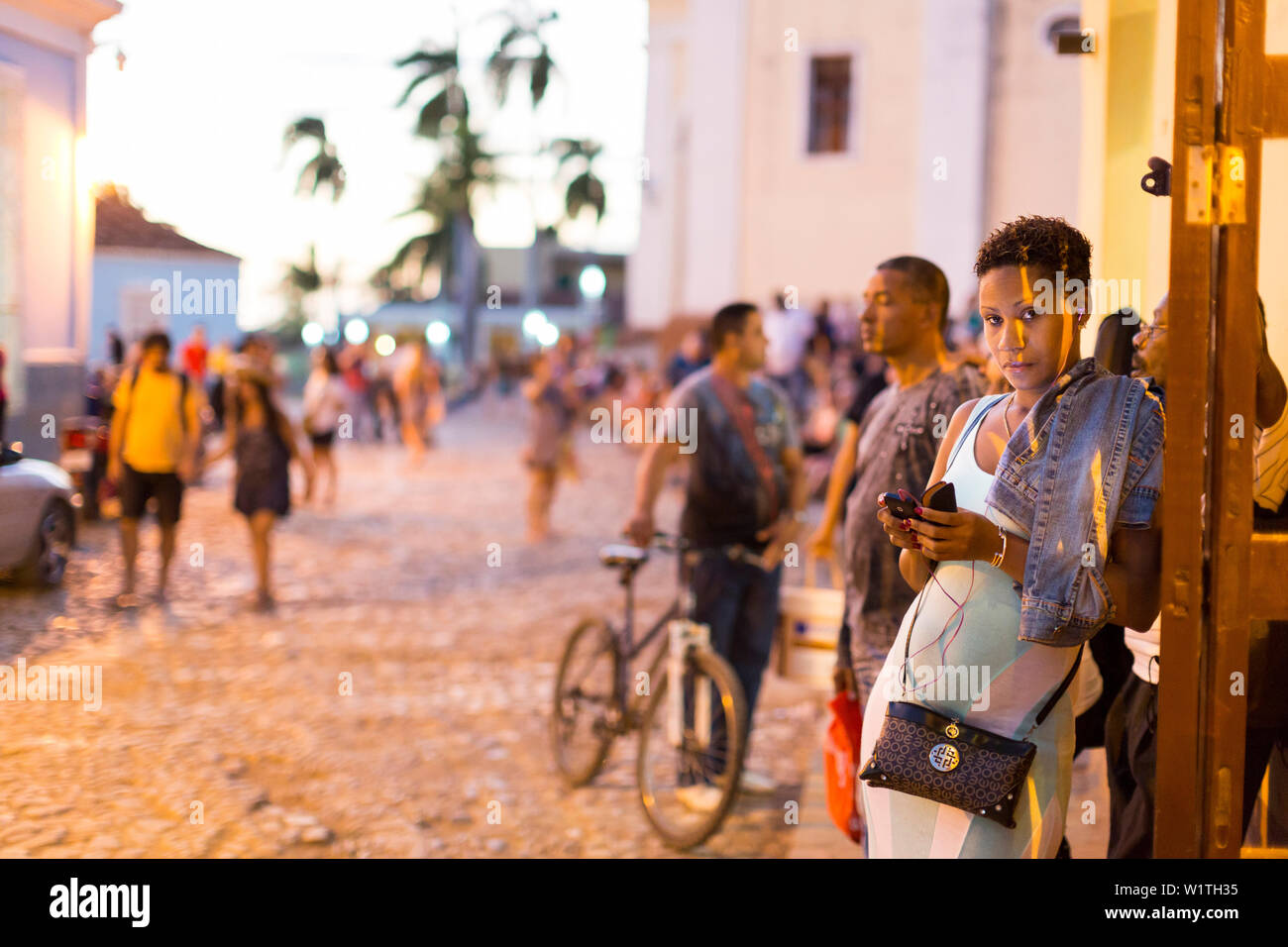 beautiful Cuban woman on her mobile at the terraces of Trinidad, next to the Iglesia Parroquial de la Santisima Trinidad close to Plaza Mayor, interne - Stock Image