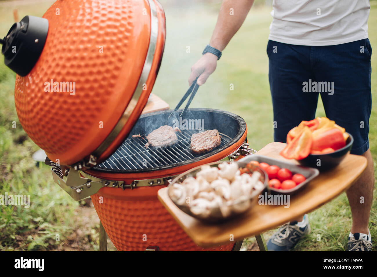 Unrecognizable man cooking meat on grill.Table with sliced mushrooms and vegetables. Summer picnic party. - Stock Image